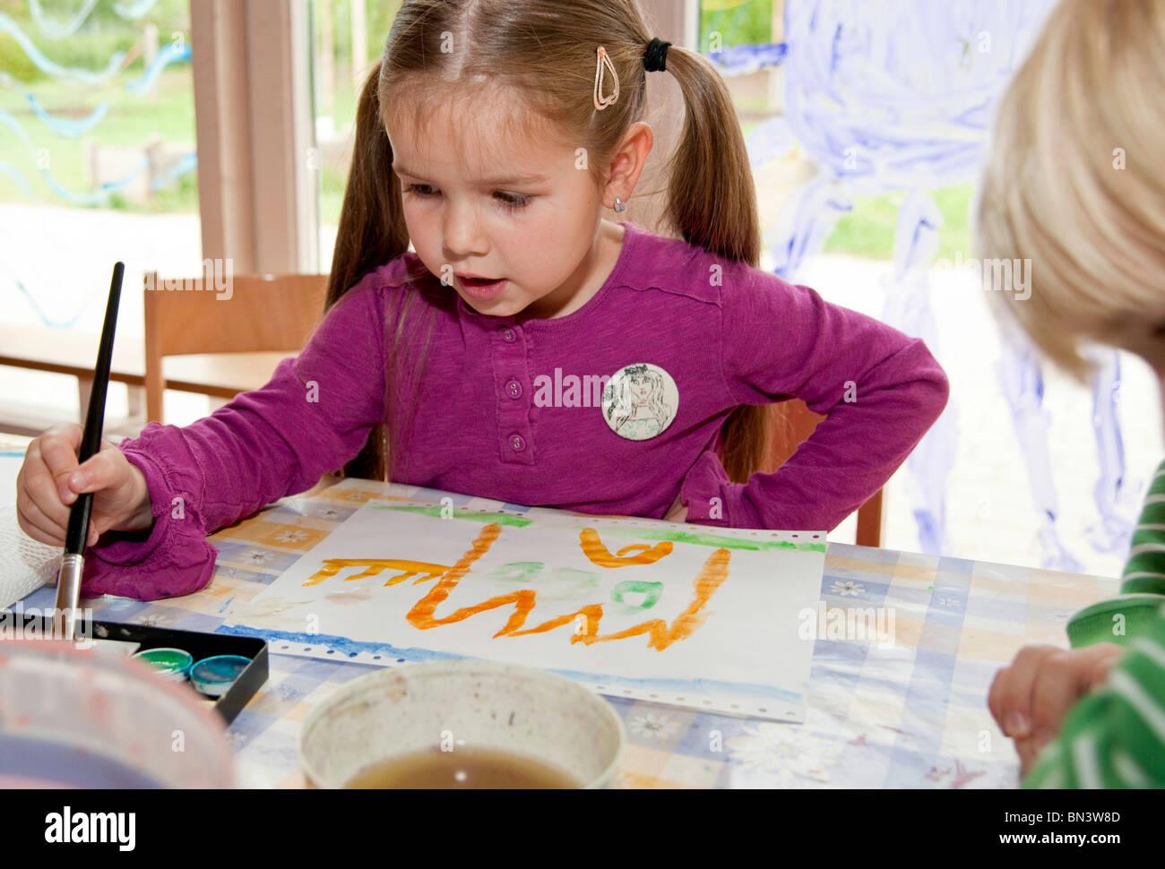 Chico y chica pintando en el kindergarten Foto de stock