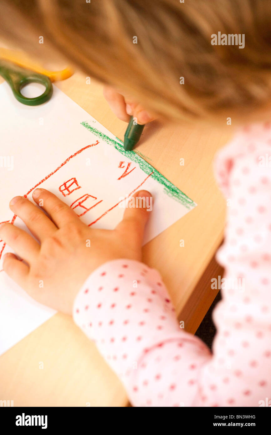 Niña dibujando una imagen con un lápiz de cera, close-up Foto de stock