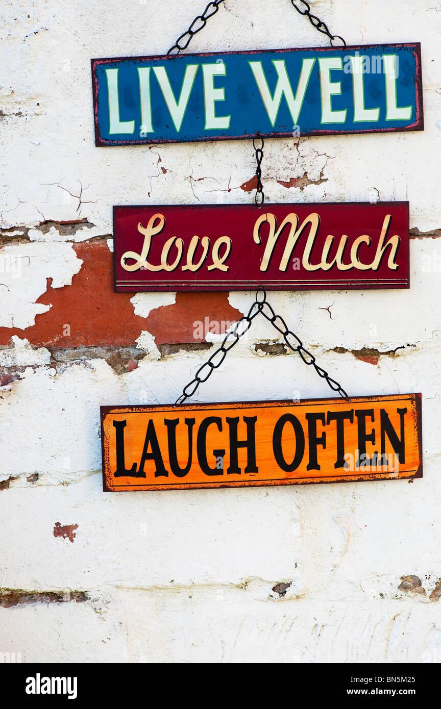 Vivir, amar, reír, metal viejo jardín signos en una pared de ladrillo pintado Imagen De Stock