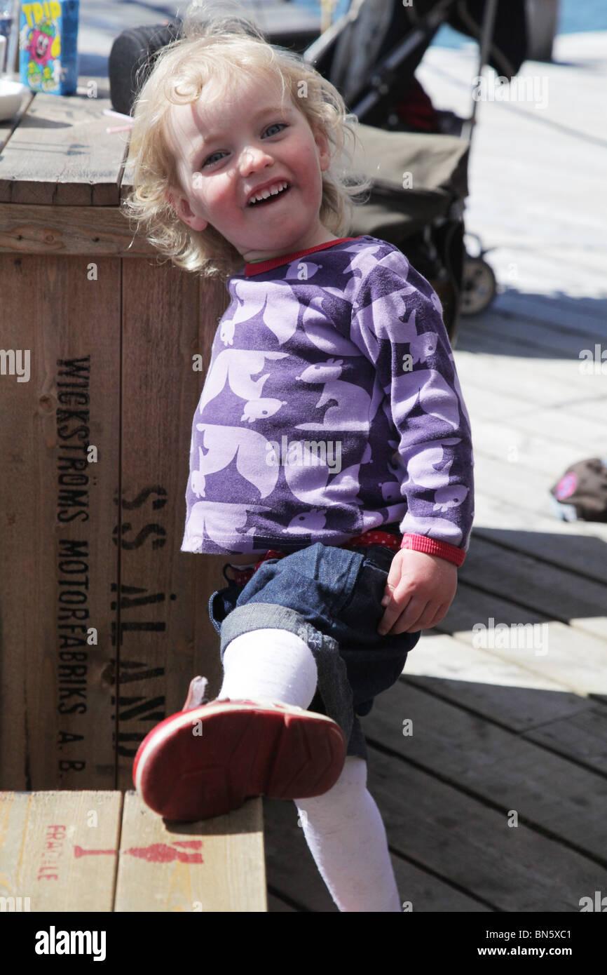 e495bd0835 Lindo bebé niña niño en pantalones cortos vestidos de rojo zapatos plantea  con gran sonrisa rizos para el modelo de cámara liberado