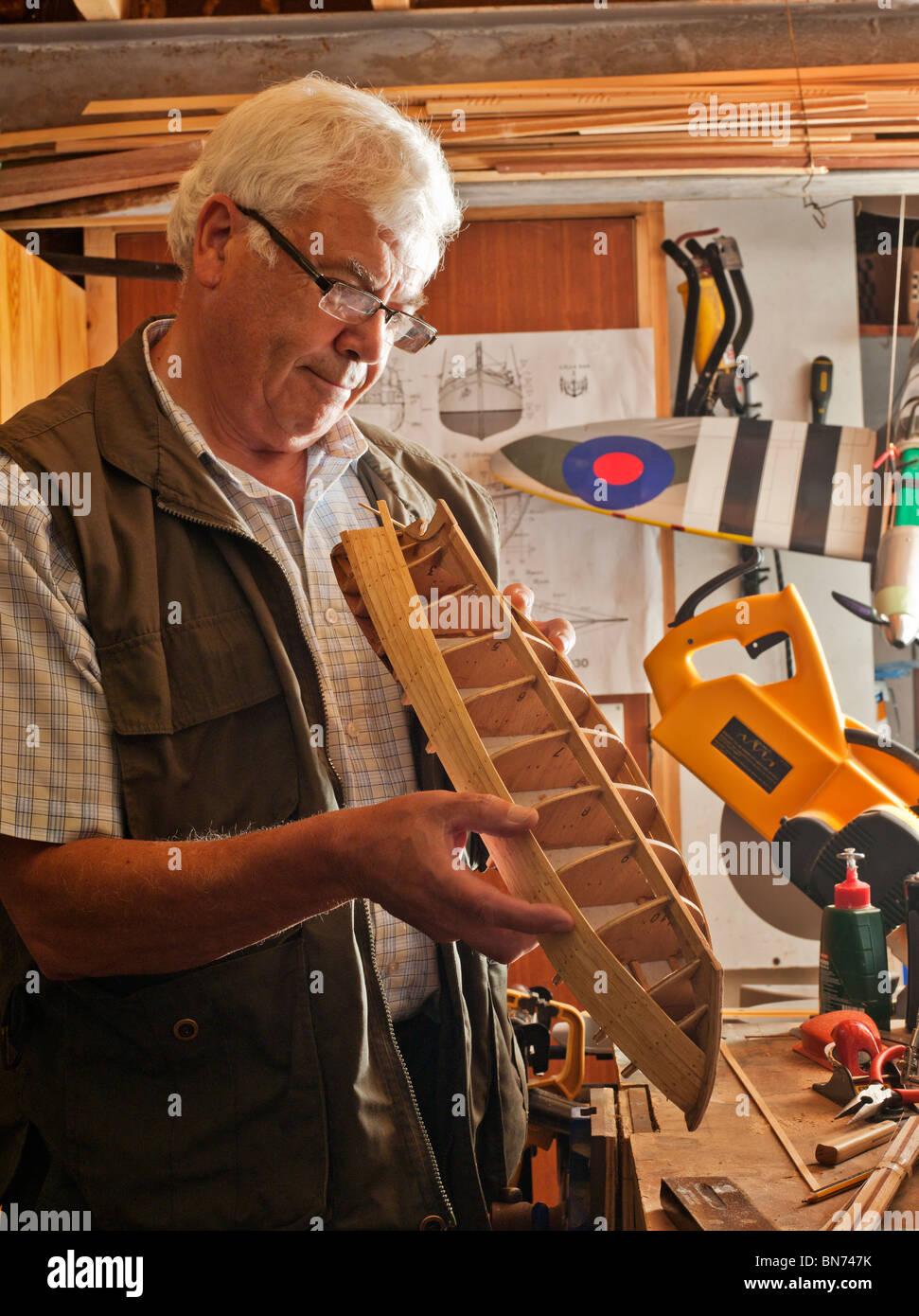 Hombre jubilado haciendo barco modelo de madera. Foto de stock