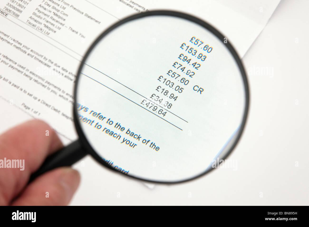 Persona con una lupa para mirar una gran factura de la tarjeta de crédito. Imagen De Stock