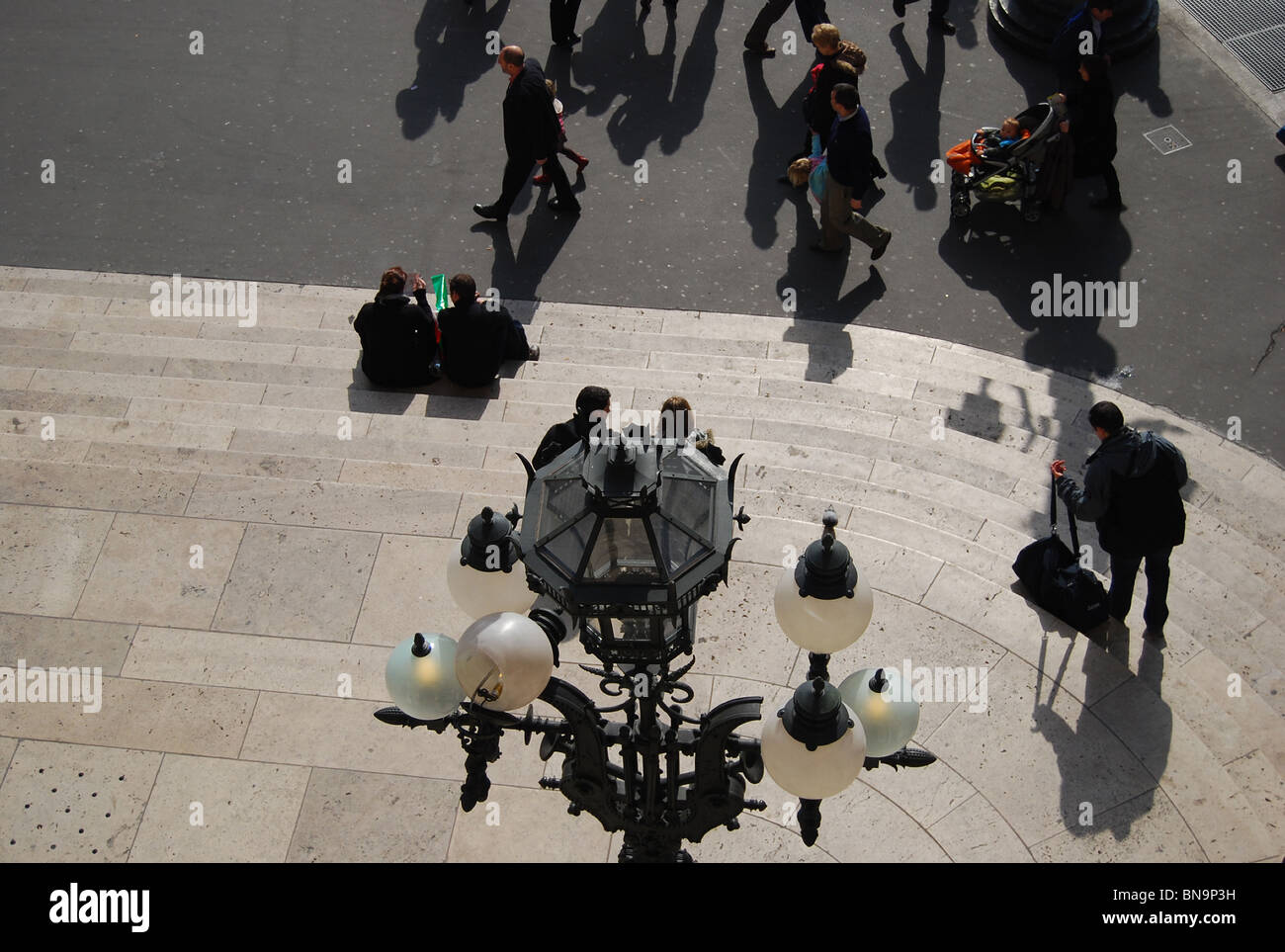 Las parejas sentada en los escalones de L'Opera por debajo de una lámpara ornamental estándar número 2913 Foto de stock