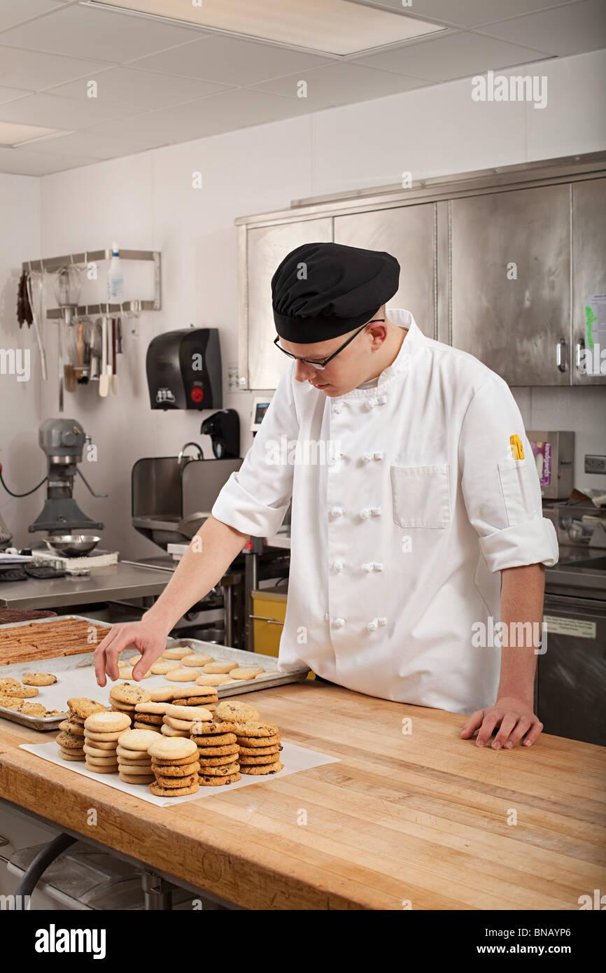 Chef macho hornear galletas en la cocina comercial Imagen De Stock
