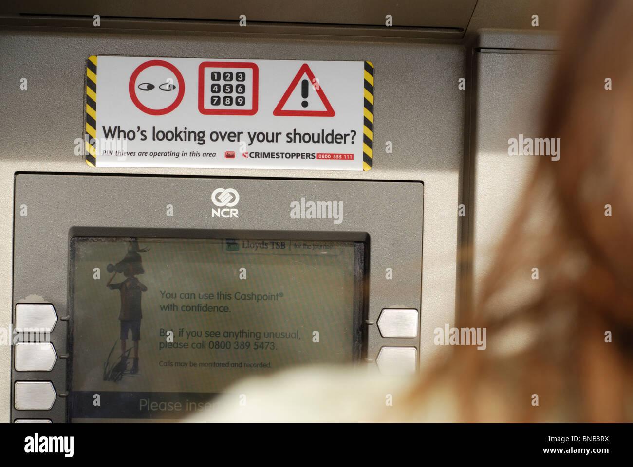 Cajero automático ATM mirando por encima del hombro Imagen De Stock