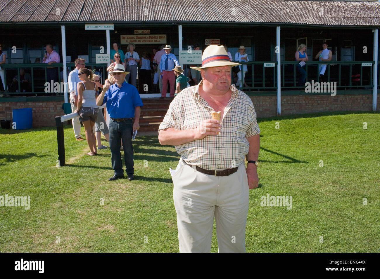 Un hombre gordo en camisa de manga corta y sombrero de paja se come un helado en un evento en un caluroso día Imagen De Stock