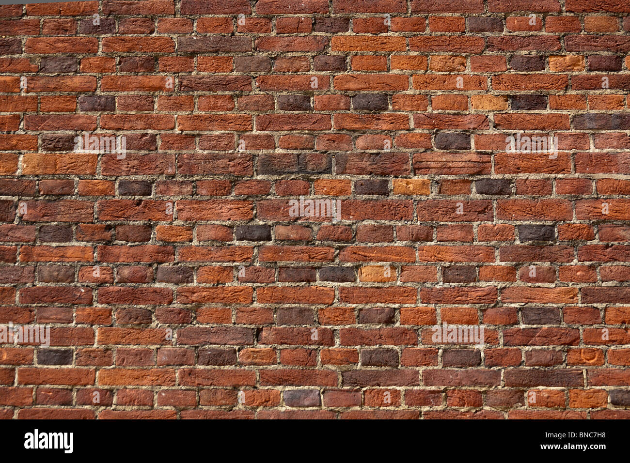 Pared de ladrillo rojo. Una sección de un muro de ladrillo rojo o naranja. Buena para los fondos. Imagen De Stock