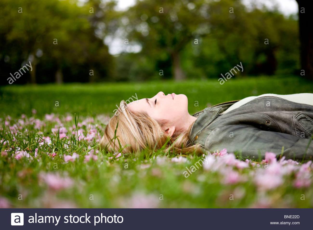 Una joven mujer recostada sobre la hierba en primavera Imagen De Stock