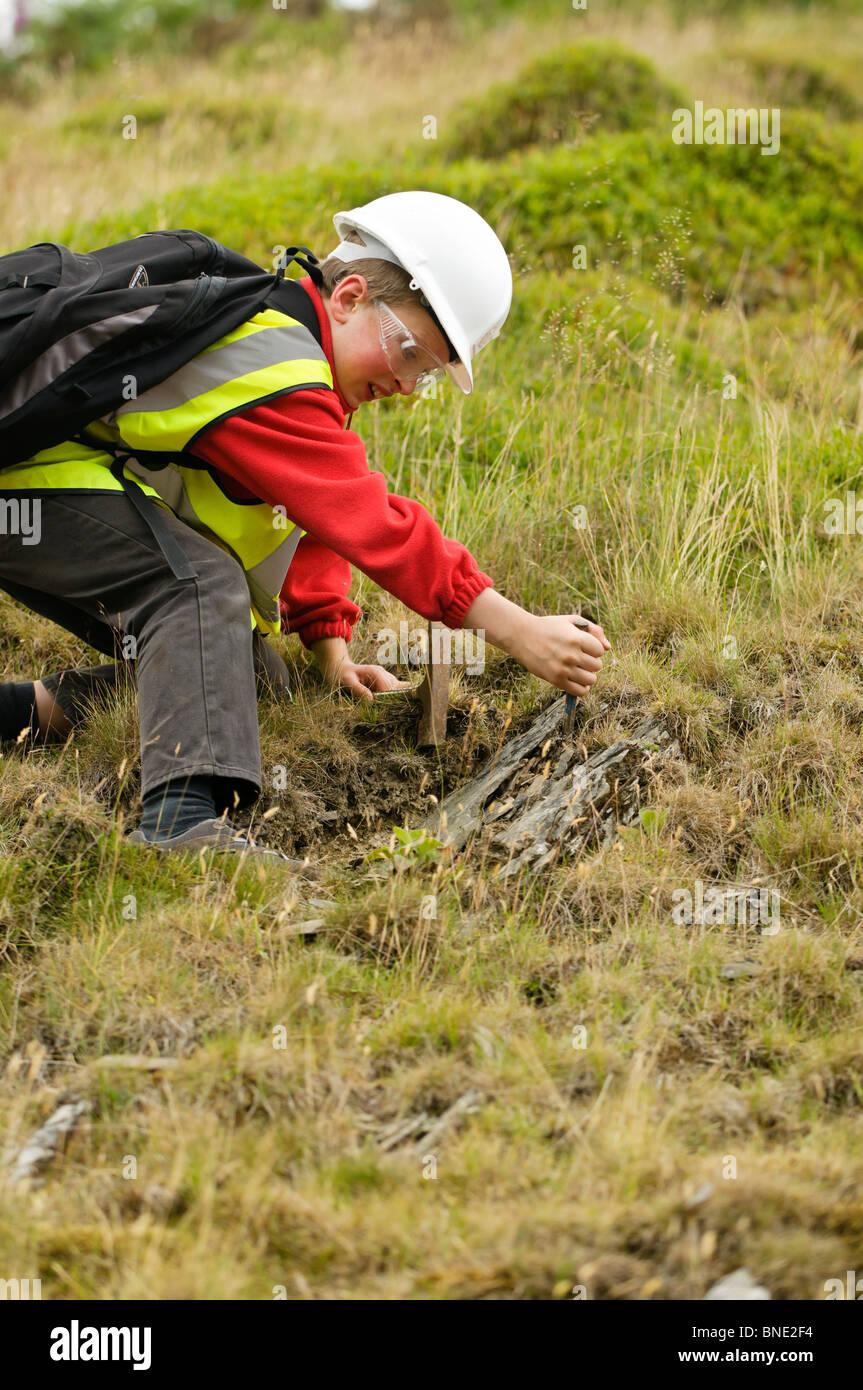 Hijo de un 'Rock Watch' viaje de campo de geología en busca de fósiles en un afloramiento de esquisto Imagen De Stock