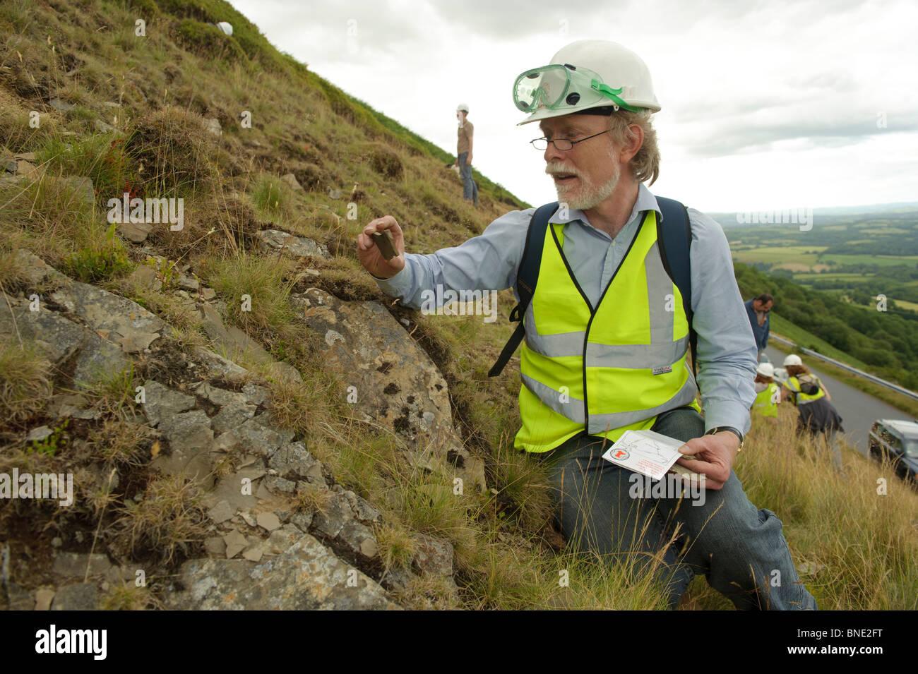 Los niños y padres en un 'Rock Watch' viaje de campo de geología en busca de fósiles en un Imagen De Stock