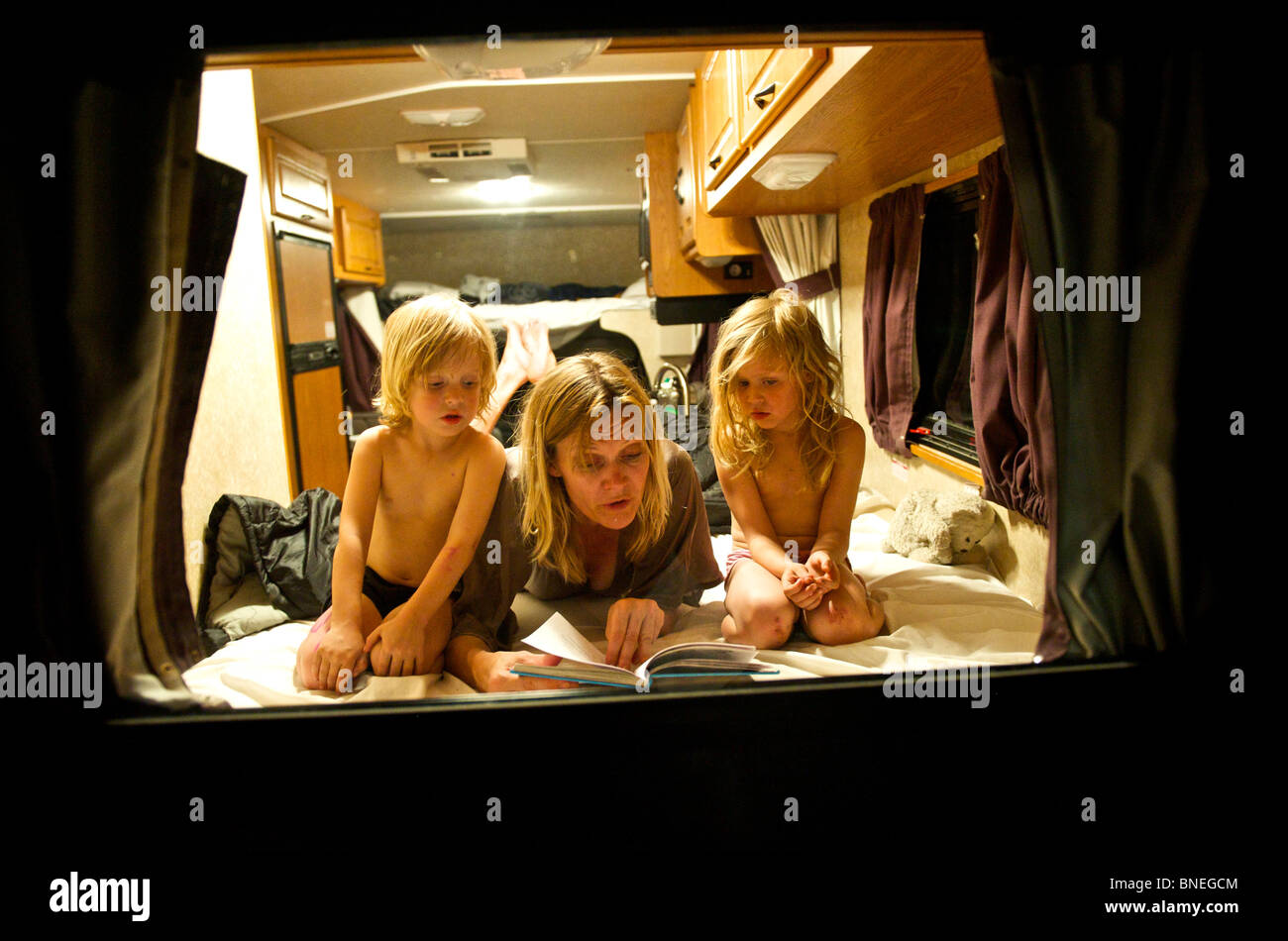 Madre leyendo un cuento a sus hijos en un RV autocaravanas en Texas, EE.UU. Foto de stock