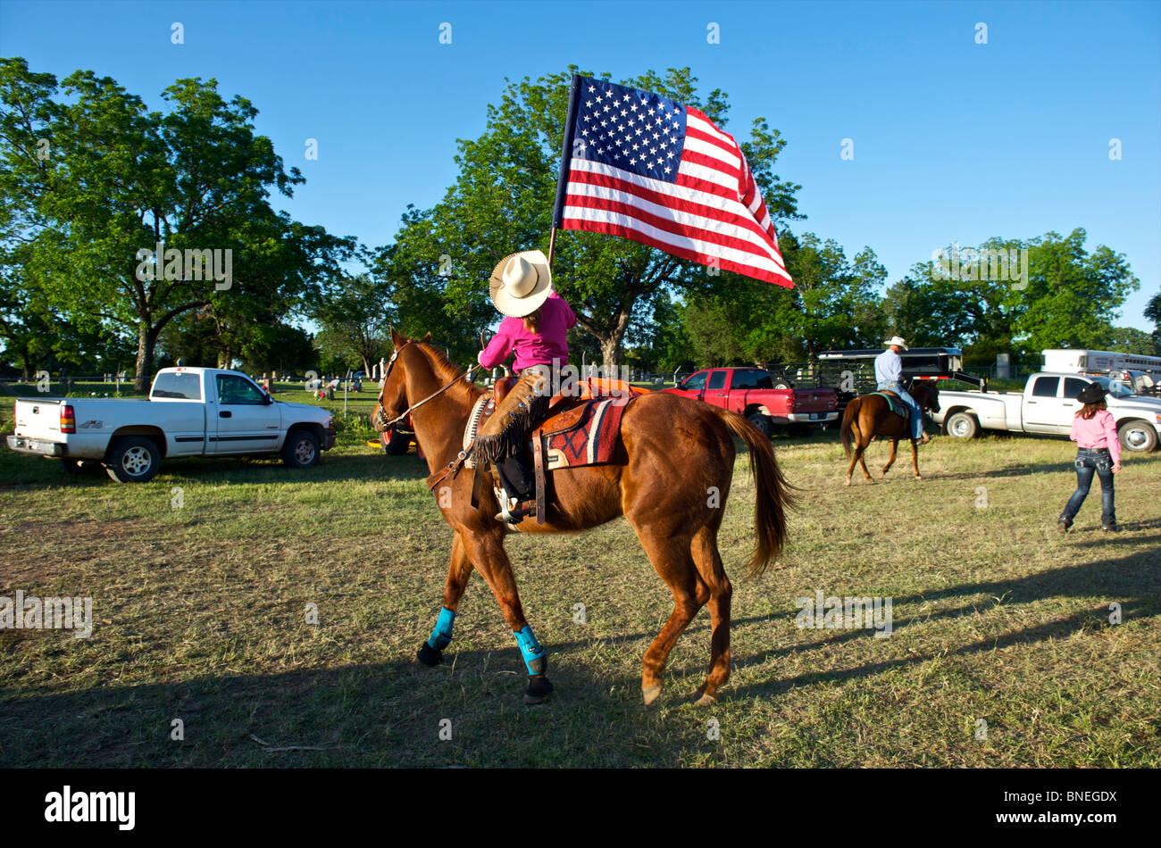 Cowgirl ondeando la bandera en la zona de depósito antes de la ceremonia de apertura del evento PRCA Rodeo en Texas, EE.UU. Foto de stock