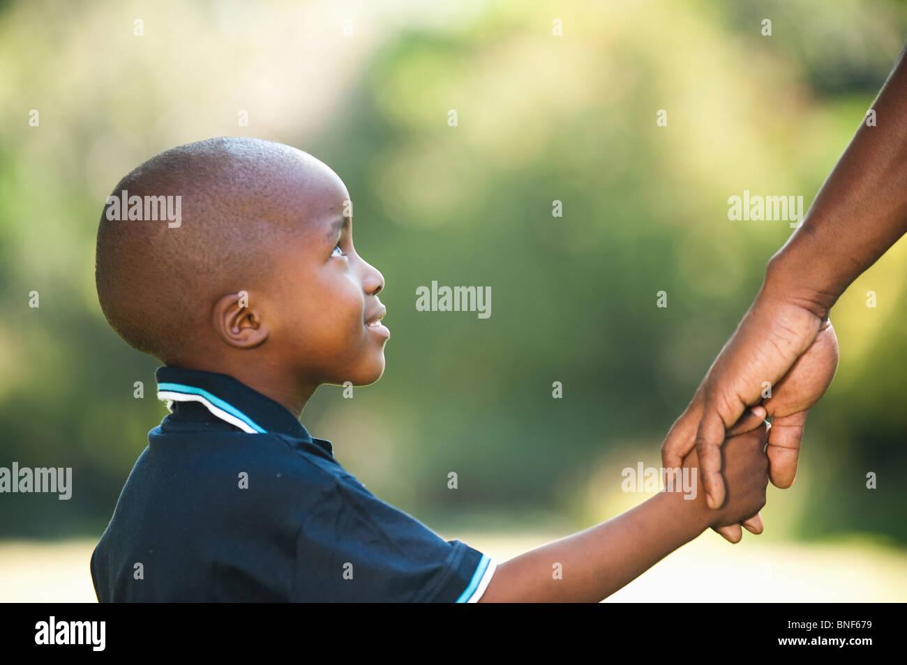 Boy (4-5) celebración padres mano, Johannesburgo, en la provincia de Gauteng, Sudáfrica Imagen De Stock