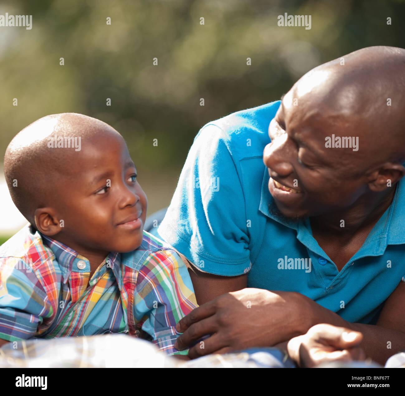 El padre y el hijo (4-5) relajarse al aire libre, Johannesburgo, en la provincia de Gauteng, Sudáfrica Imagen De Stock