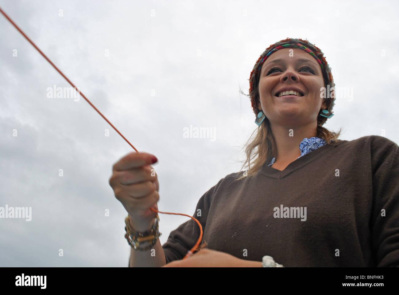 Una niña de la pesca de la caballa en un viaje de pesca fuera de Lyme Regis, Dorset, Inglaterra Imagen De Stock