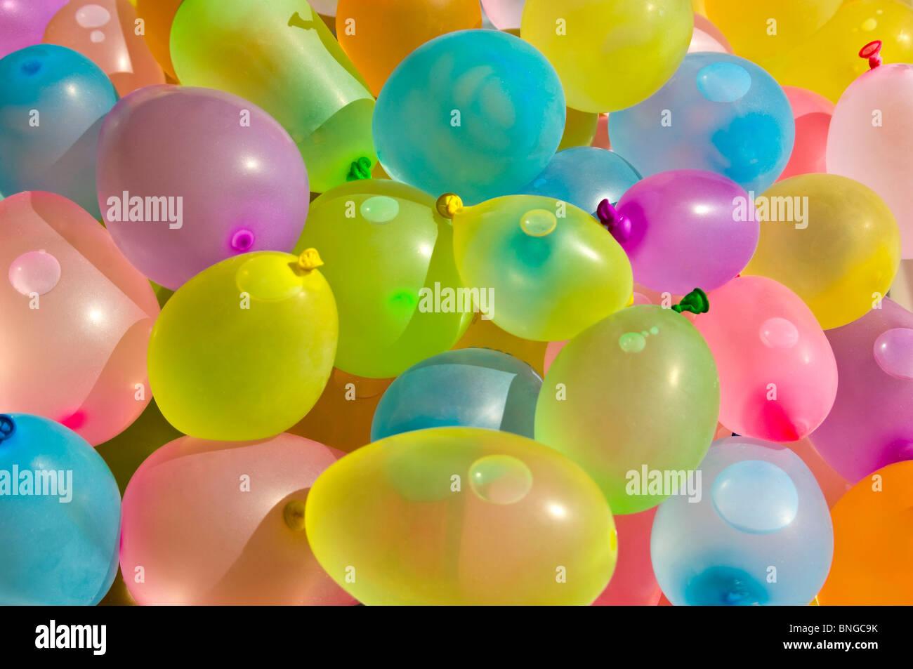 Cierre horizontal de cientos de coloridos globos llenos de látex con agua en preparación de una guerra Imagen De Stock