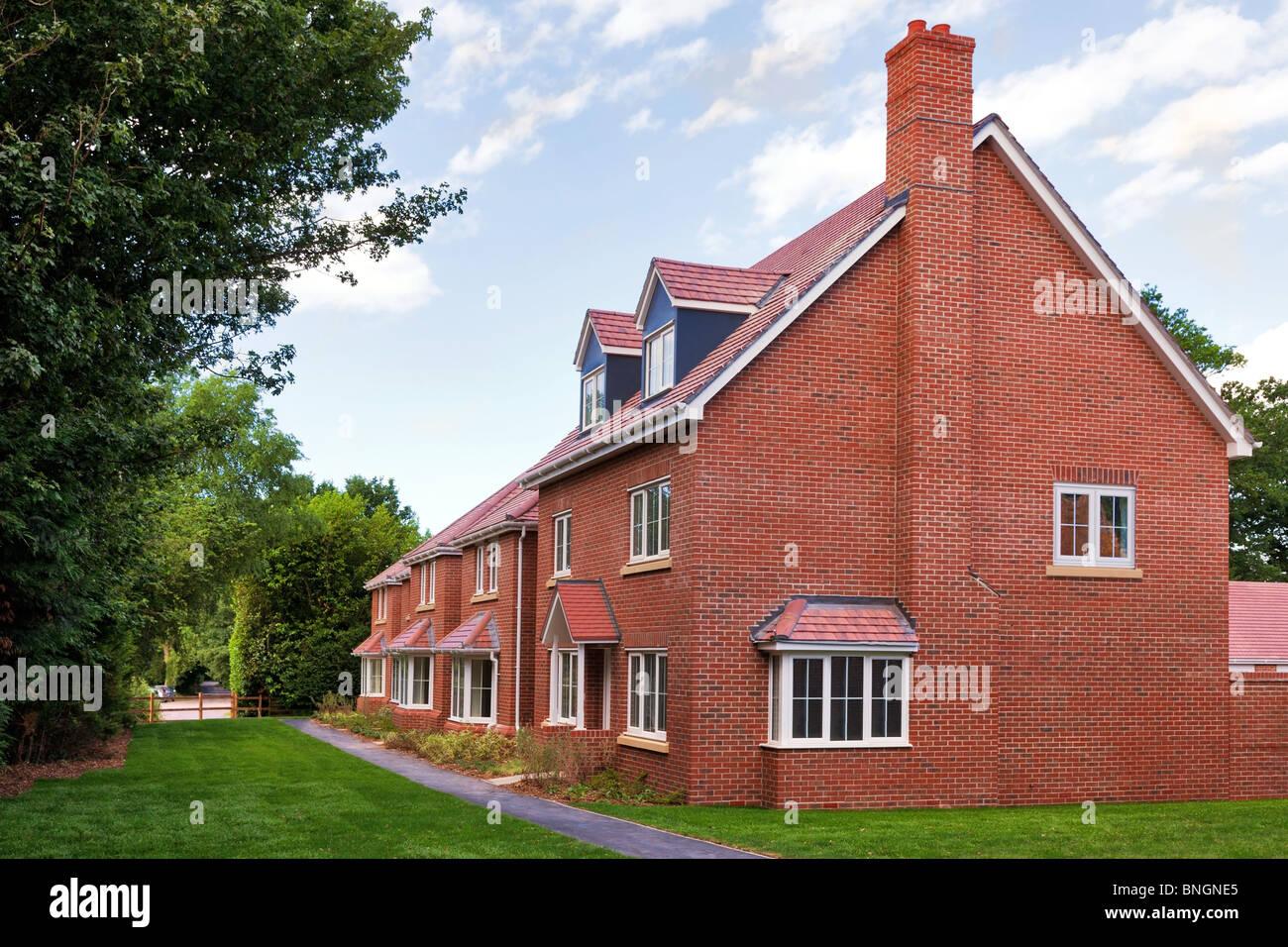 Una hilera de casas de ladrillo rojo nueva vacía en un moderno desarrollo inmobiliario de vivienda del Reino Imagen De Stock