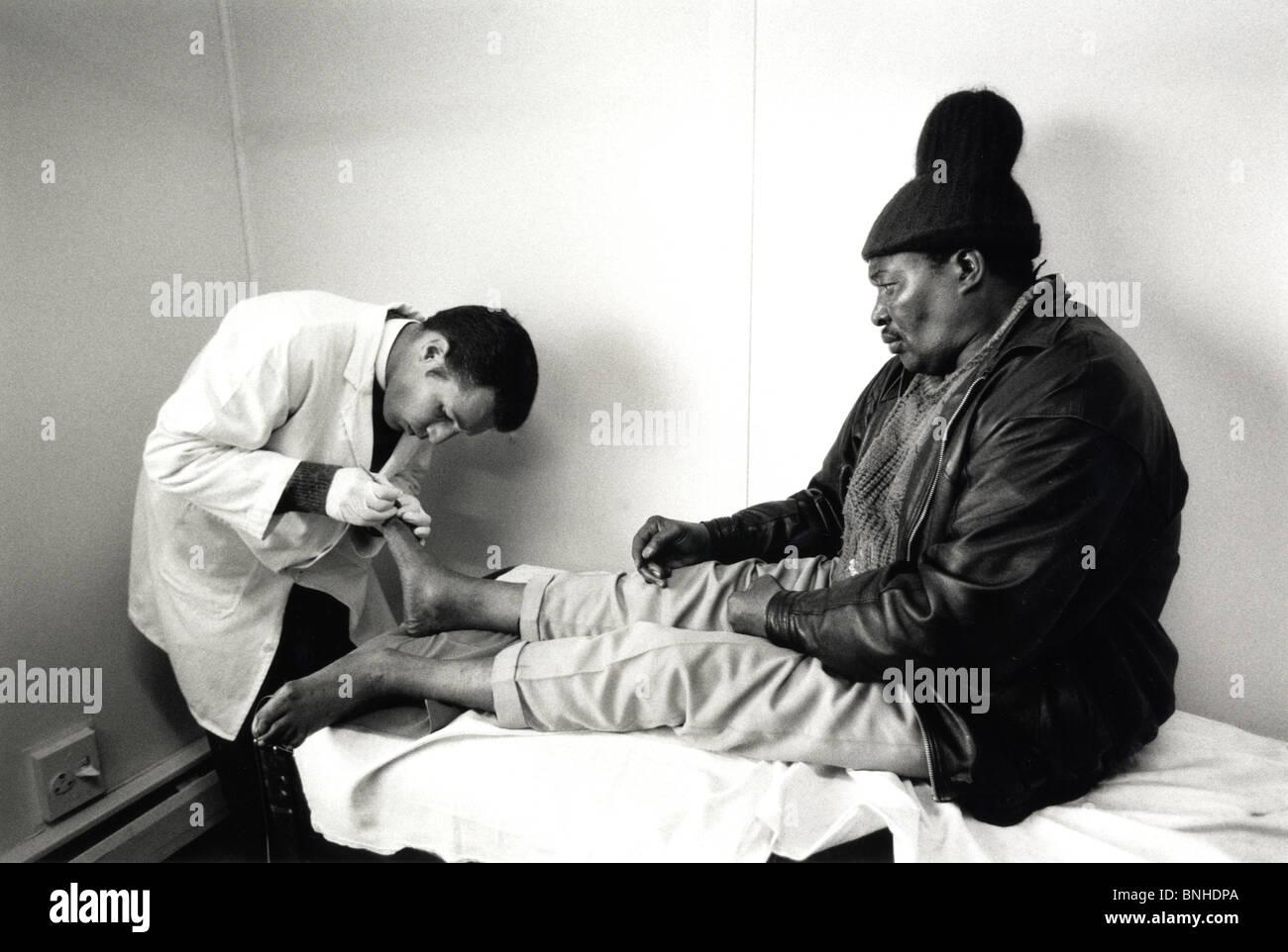 Blanco macho joven doctor examina los pies de un anciano negro en un paciente de sexo masculino de podiatría Imagen De Stock
