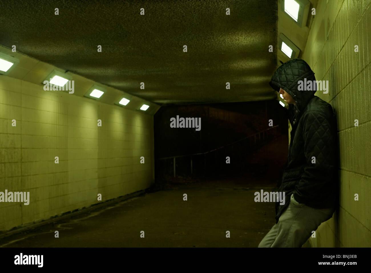 Adolescente, apoyada contra la pared de metro durante la noche. Imagen De Stock