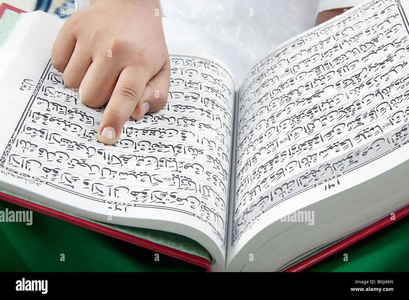 Muslim chico leyendo el Corán Imagen De Stock