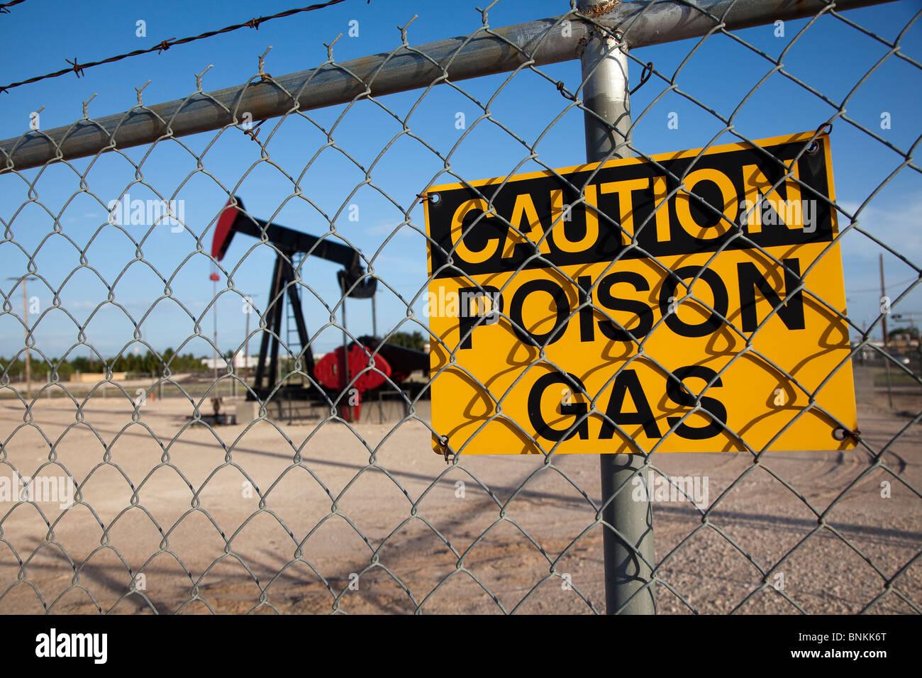 Precaución signo gas venenoso en el cerco alrededor de la bomba de aceite asintiendo con Jenny Monahan Texas USA Foto de stock
