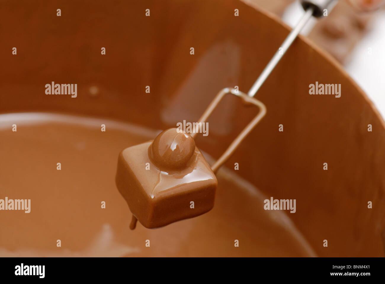 Fabricación de chocolates, blanco se sumerge en el chocolate Imagen De Stock