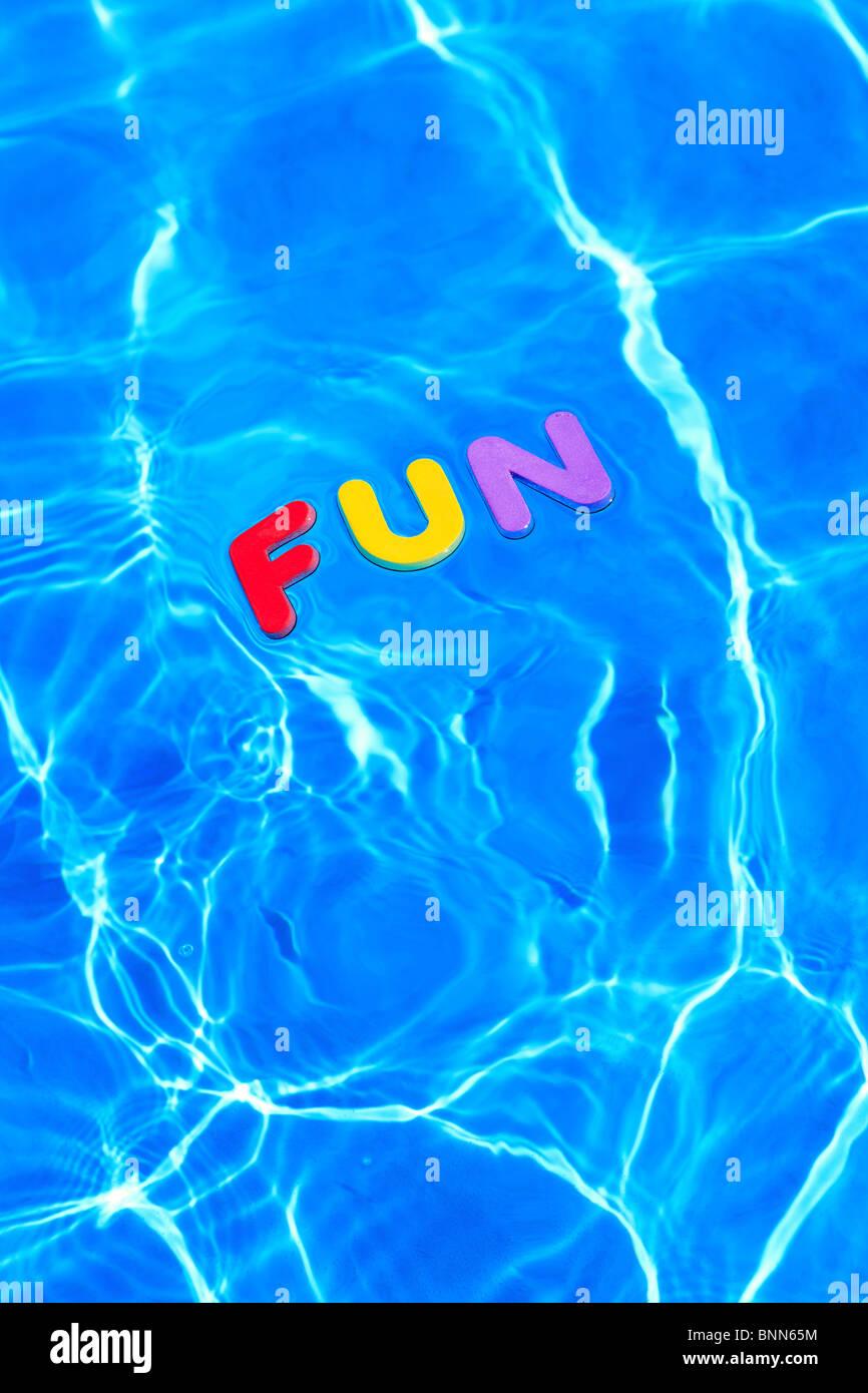La palabra diversión hechas de espuma letras flotando sobre la superficie del agua de una piscina Imagen De Stock
