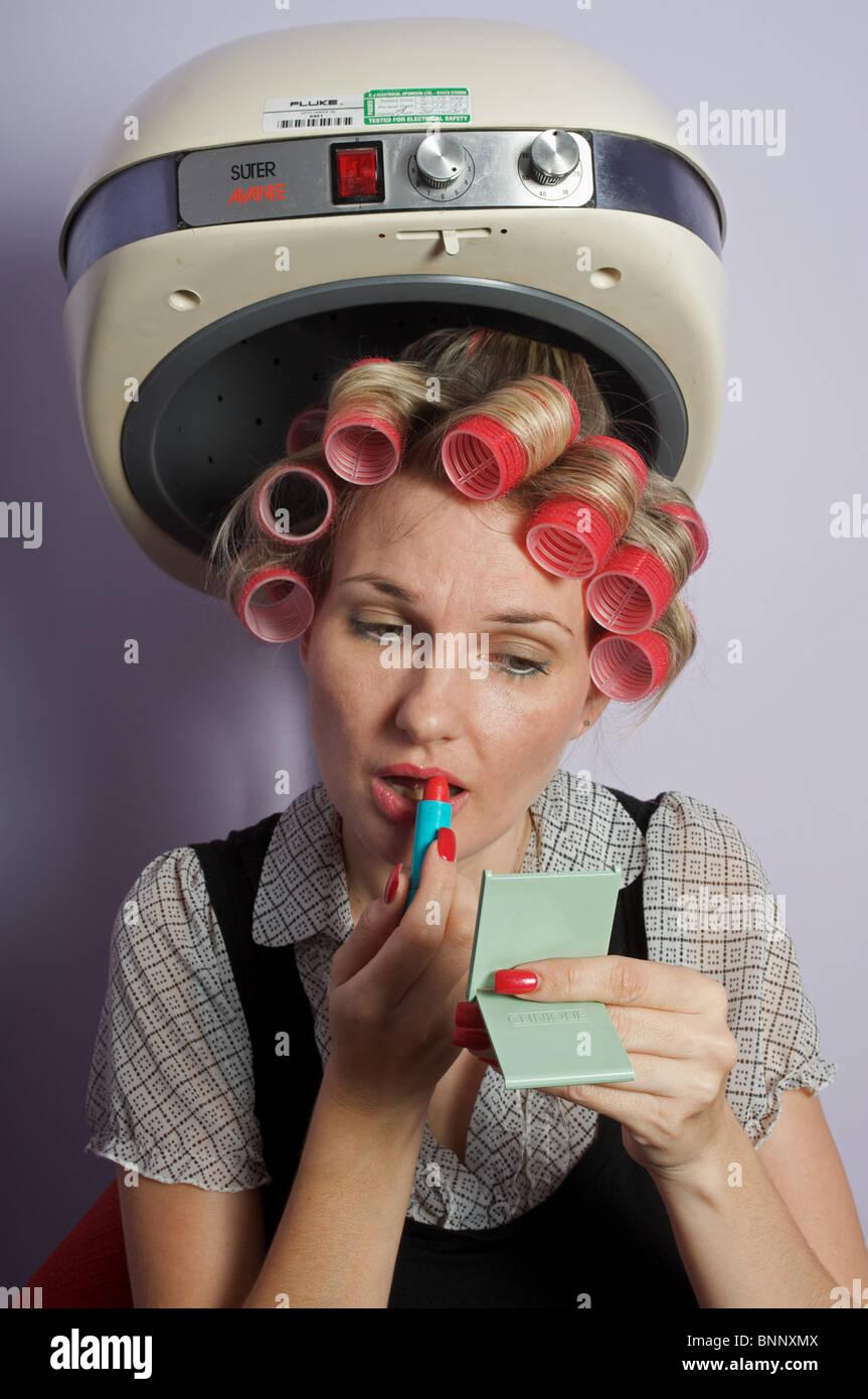 Mujer en rulos bajo secador aplico maquillaje Imagen De Stock