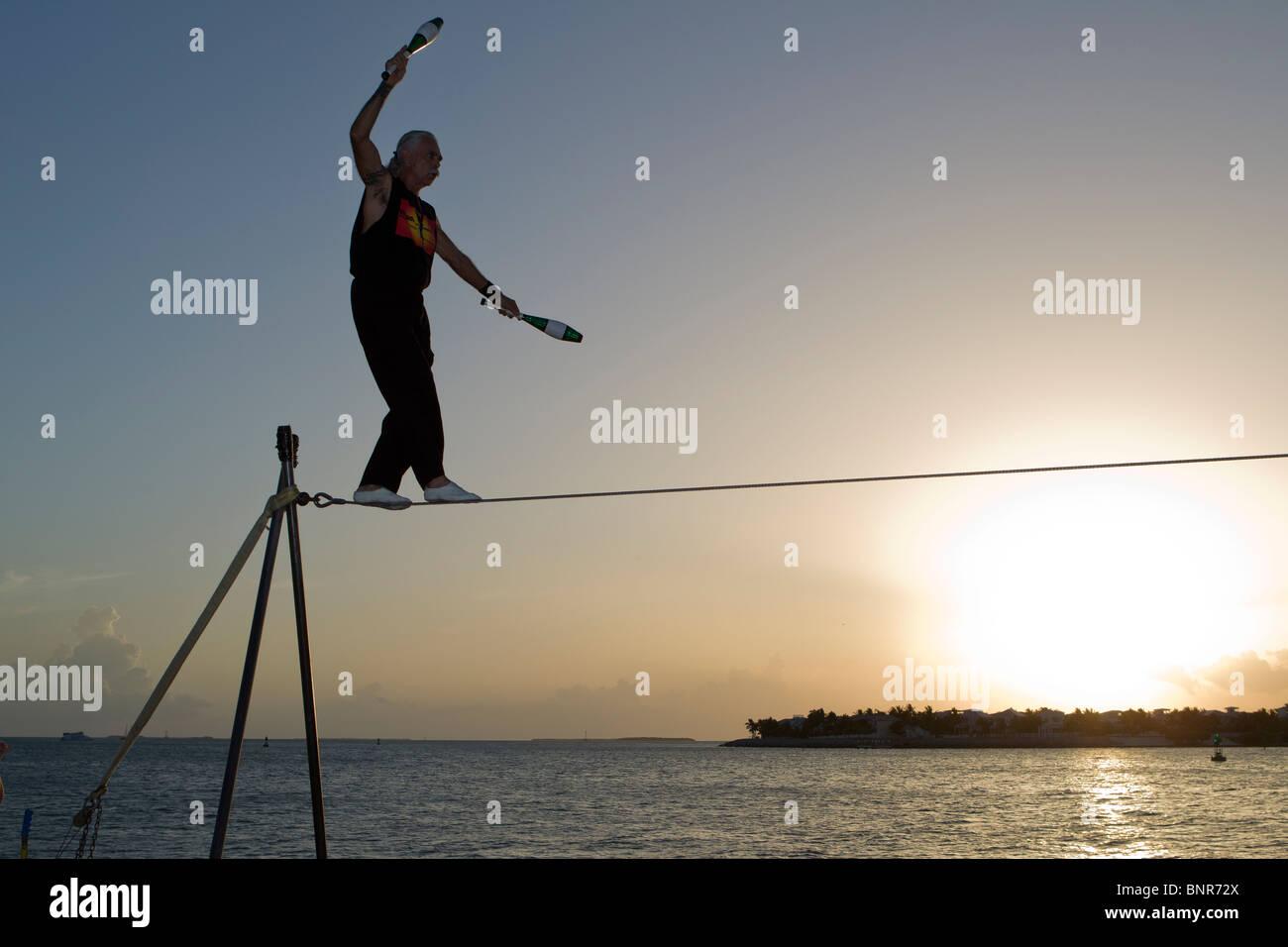 Famosa Sunset Celebration, Key West, Florida. Ejecutante de la calle, Soto sobre el alambre alto. Foto de stock