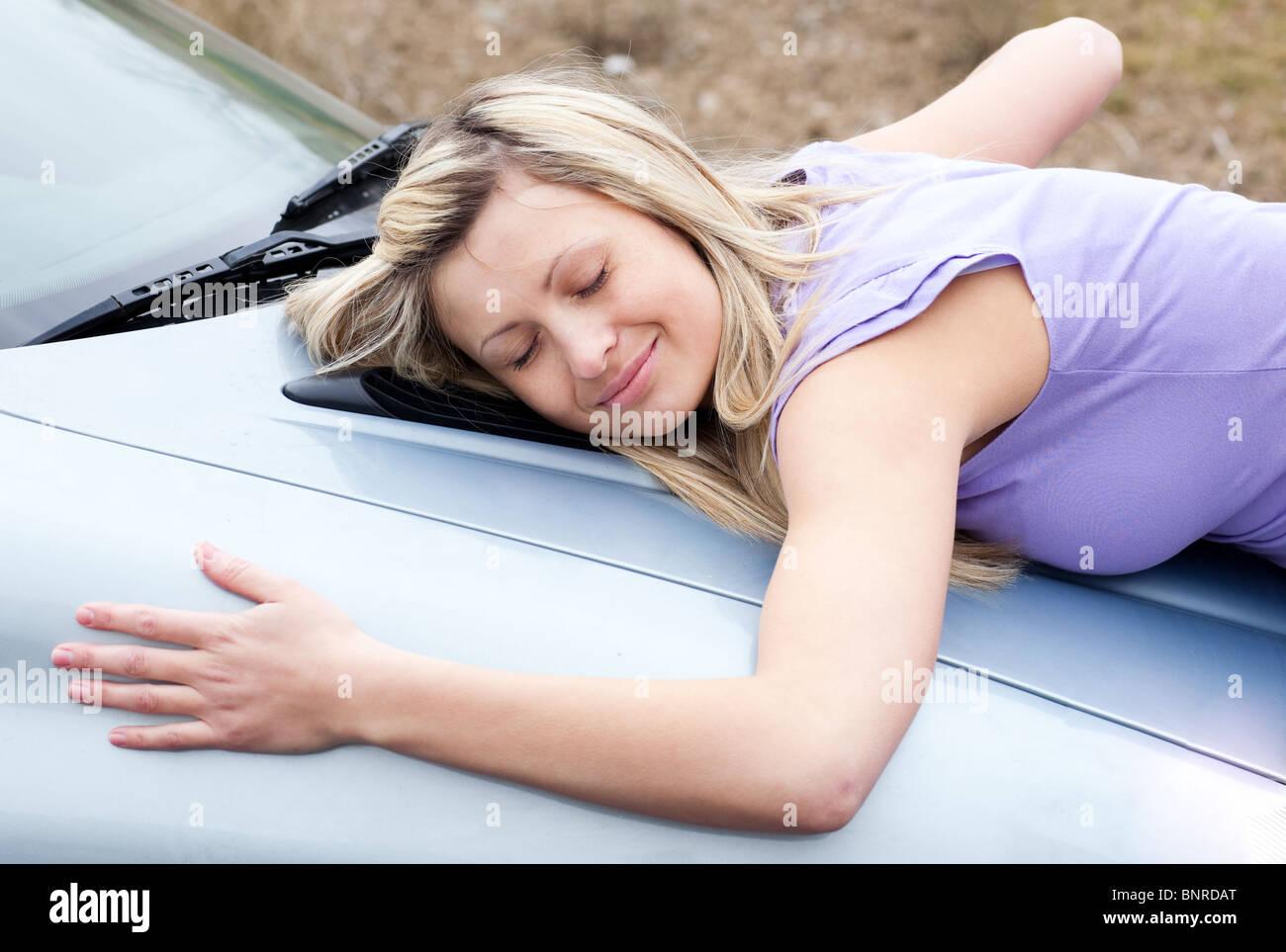 Hembra alegre conductor huging su coche nuevo Imagen De Stock