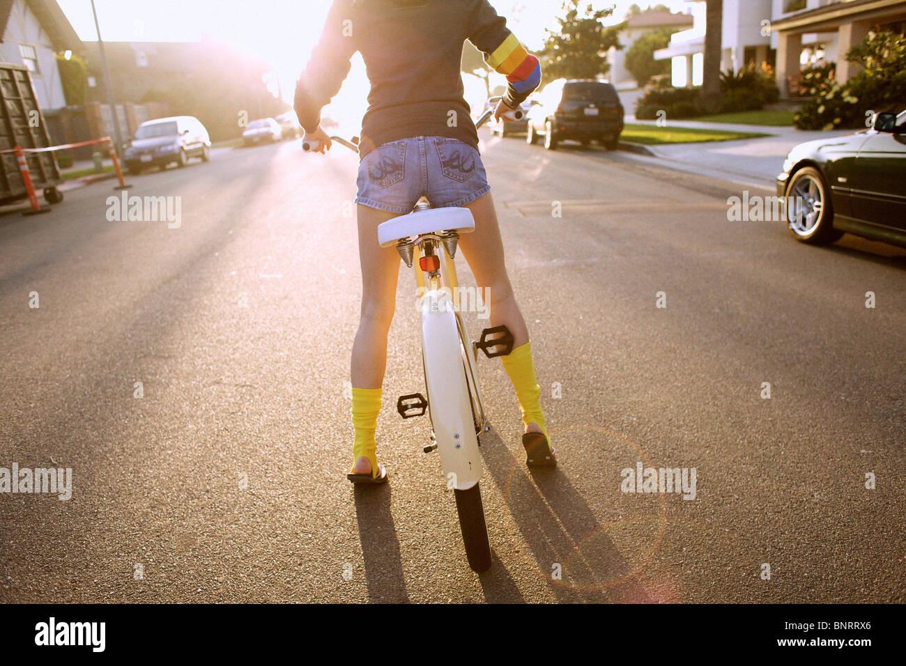 Mujer joven llevaba calcetines y una sudadera con capucha amarillo se prepara para iniciar montando una bicicleta. Imagen De Stock