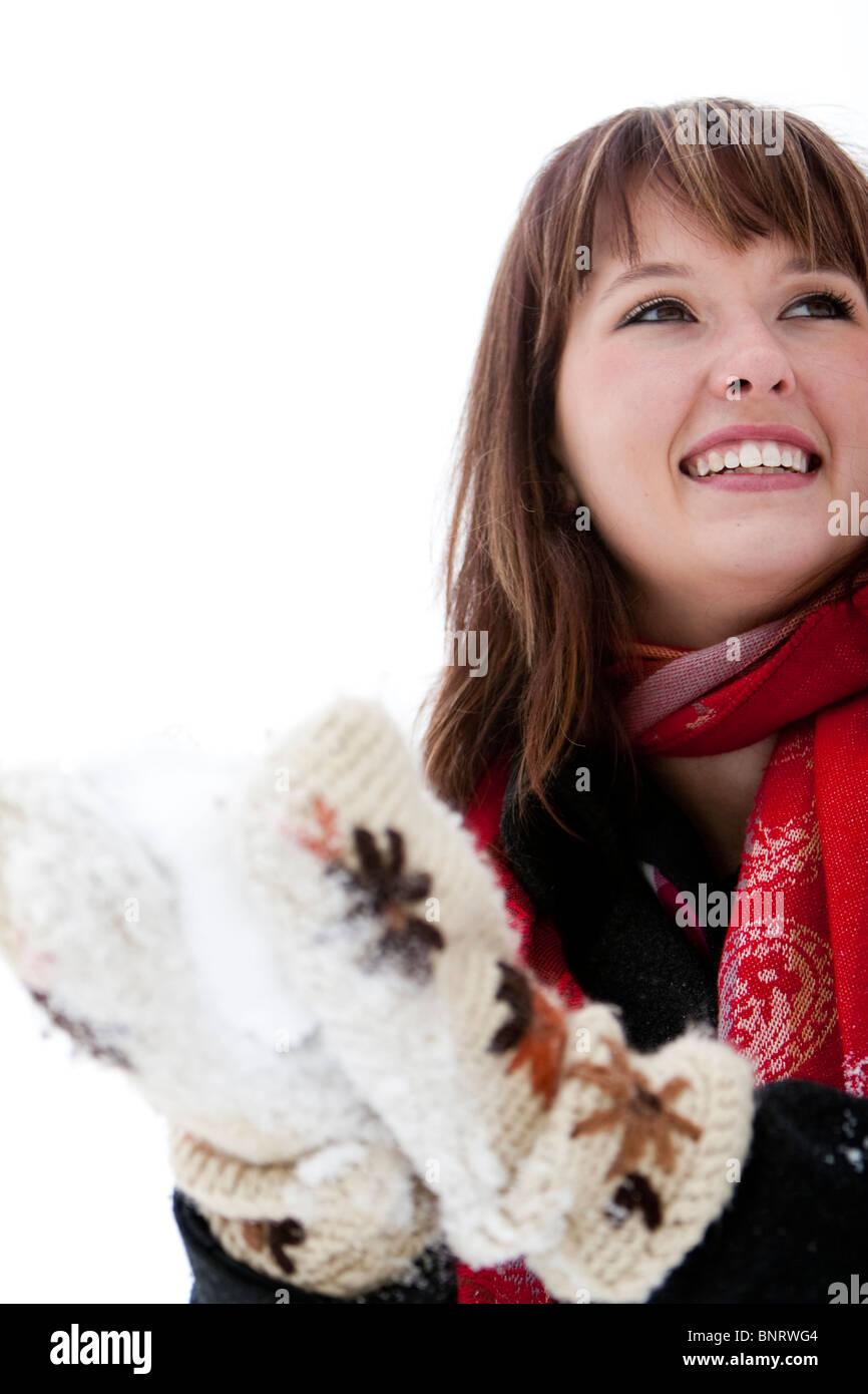 Una mujer lleva un pañuelo rojo y packs, una bola de nieve con grandes difuso en un nublado mitones tejidos Imagen De Stock