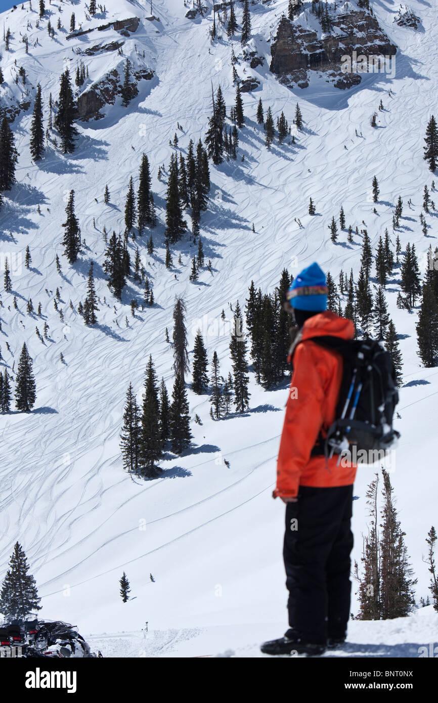Un macho snowboarder mira hacia atrás en un enorme acantilado solo entró en Utah. Imagen De Stock