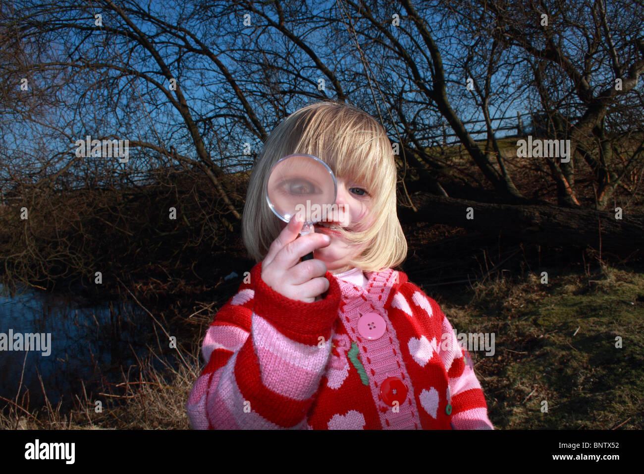 Chica (2-3) mirando a través de una lupa Imagen De Stock