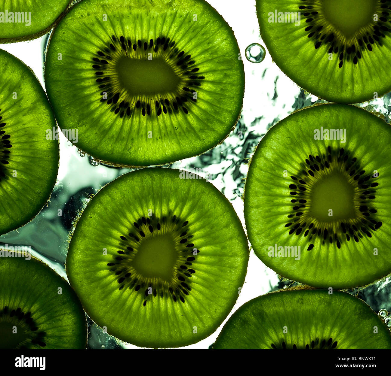 Algunas rodajas de kiwi maduro en la superficie húmeda Imagen De Stock