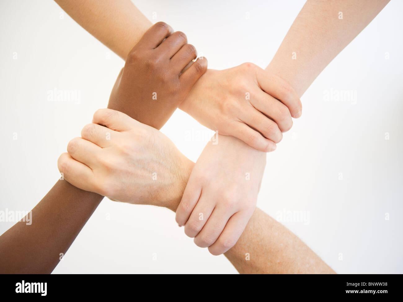 Cuatro manos sosteniendo las muñecas de otras personas Imagen De Stock