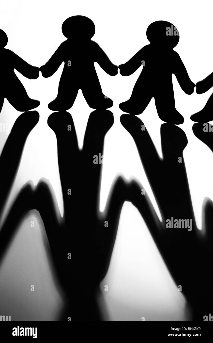 Imagen en blanco y negro de siluetas de figuras uniendo sus manos para ilustrar el concepto de apoyo y colaboración Imagen De Stock