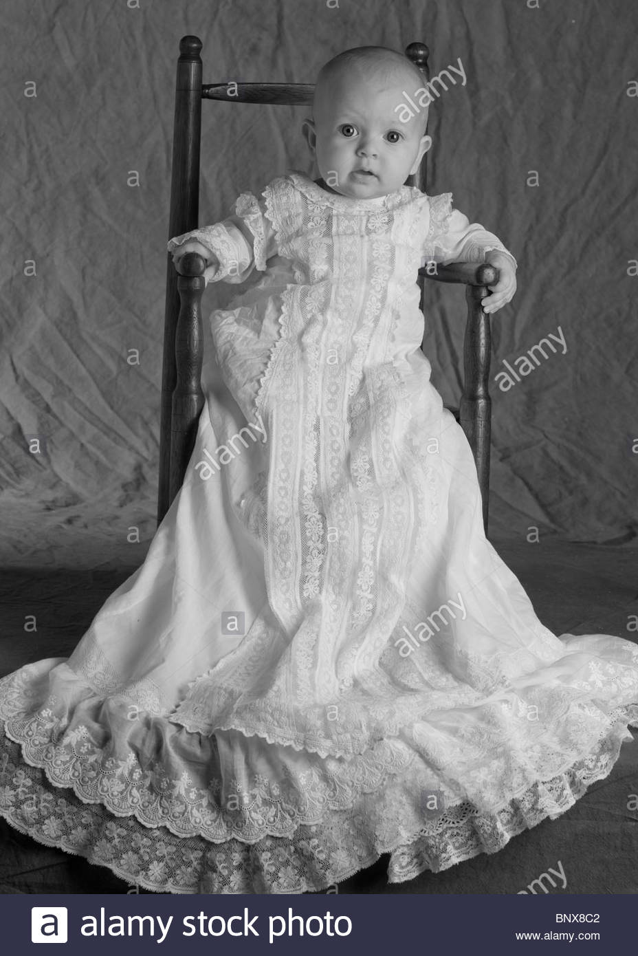953ee0601 Niña sentada en la silla antigua en su vestido de bautizo Imagen De Stock