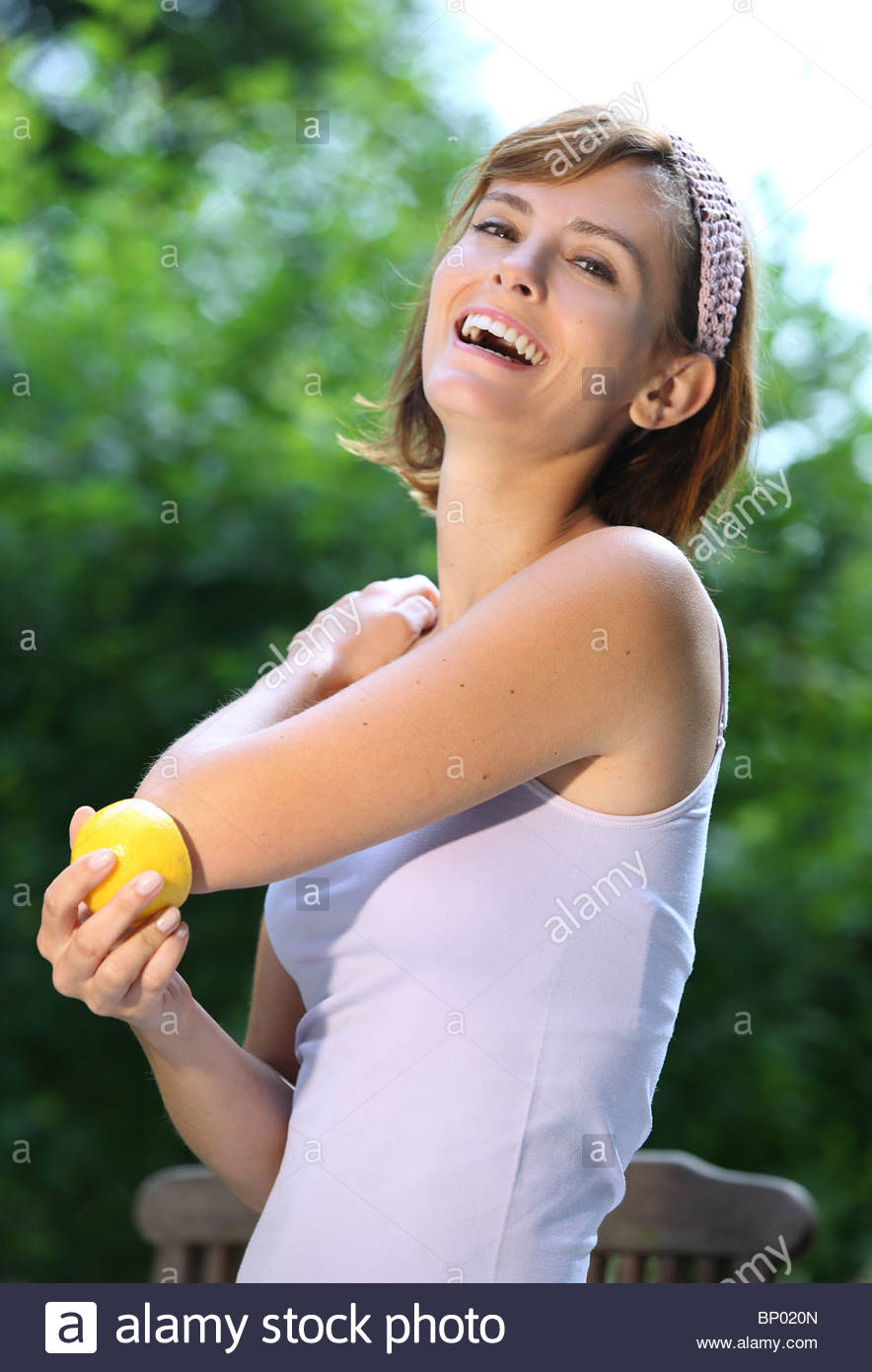 Mujer roza el codo con un limón Imagen De Stock