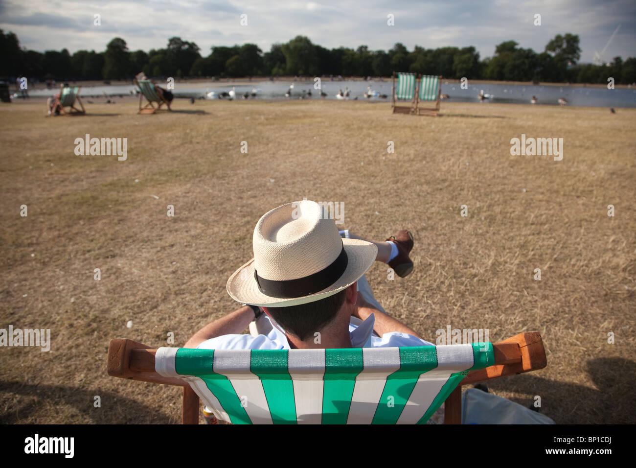 d1fb7fbc7f15e Un hombre que llevaba un sombrero de Panamá se sienta en una silla cubierta  de rayas