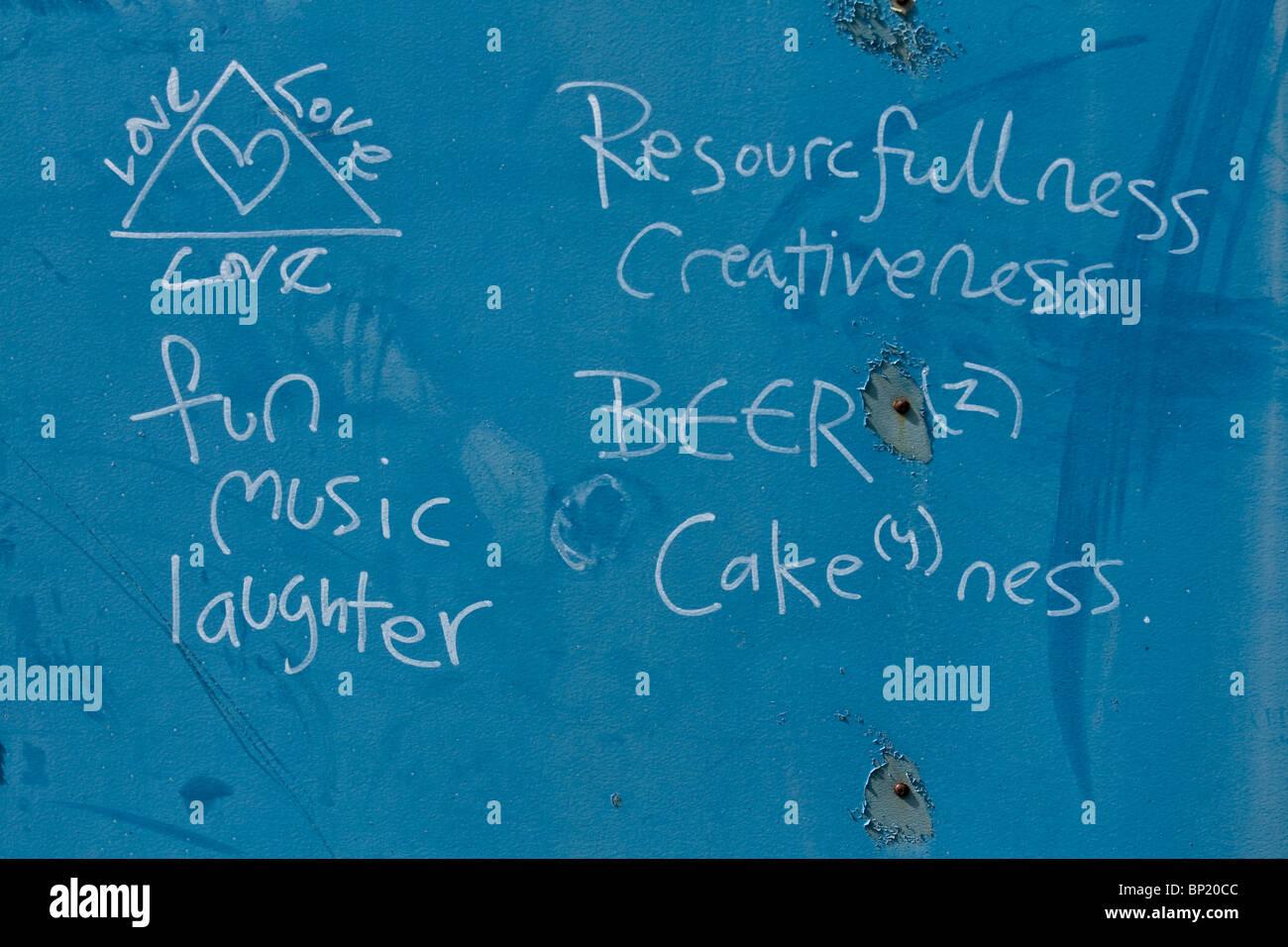 Divertido graffiti en una pared azul ensalzando el amor divertida música y risas. Y cerveza. Todo lo que necesitamos para un mundo mejor. Foto de stock