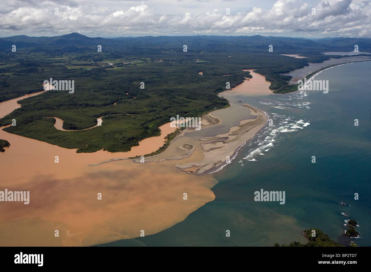 Vista aérea por encima de los sedimentos fangosos lleno río que fluye en el océano Pacífico, Imagen De Stock