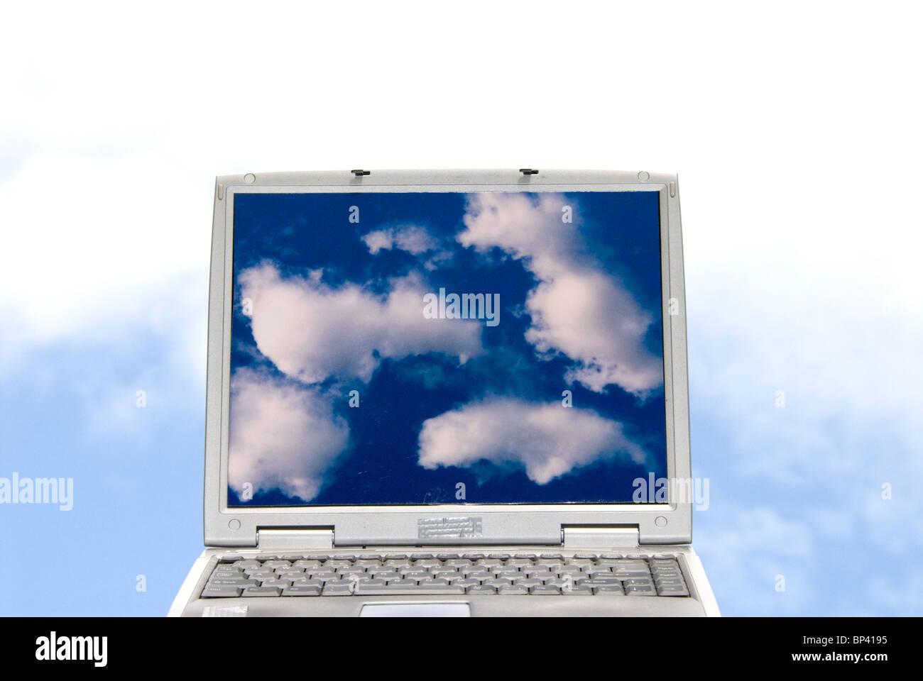 Ordenador portátil con imágenes de nubes y nubes en el fondo que representa el cloud computing Imagen De Stock