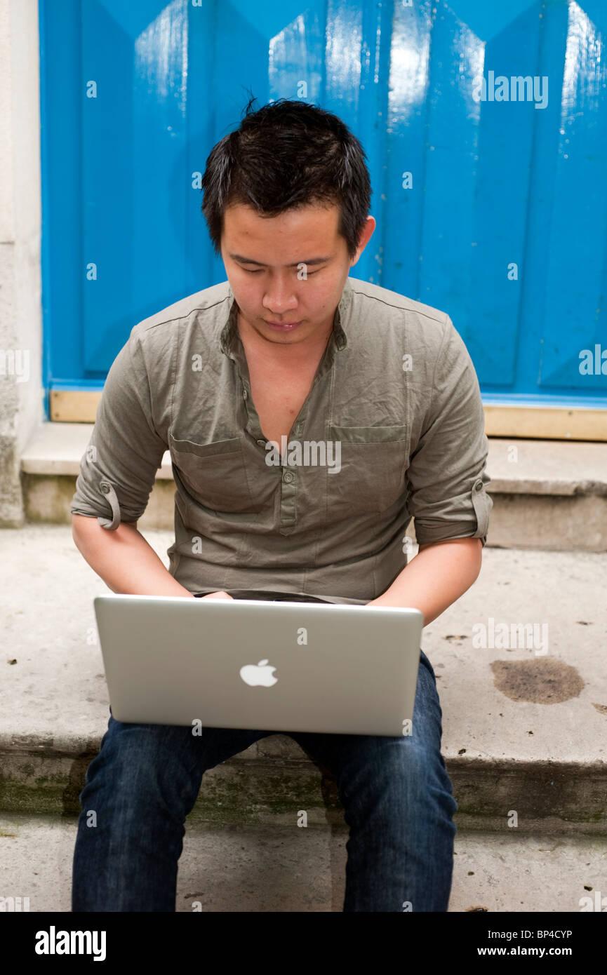 Adulto joven, hombre asiático, mirando al Ordenador Portátil, Pantalla, fuera solos en la calle Foto de stock