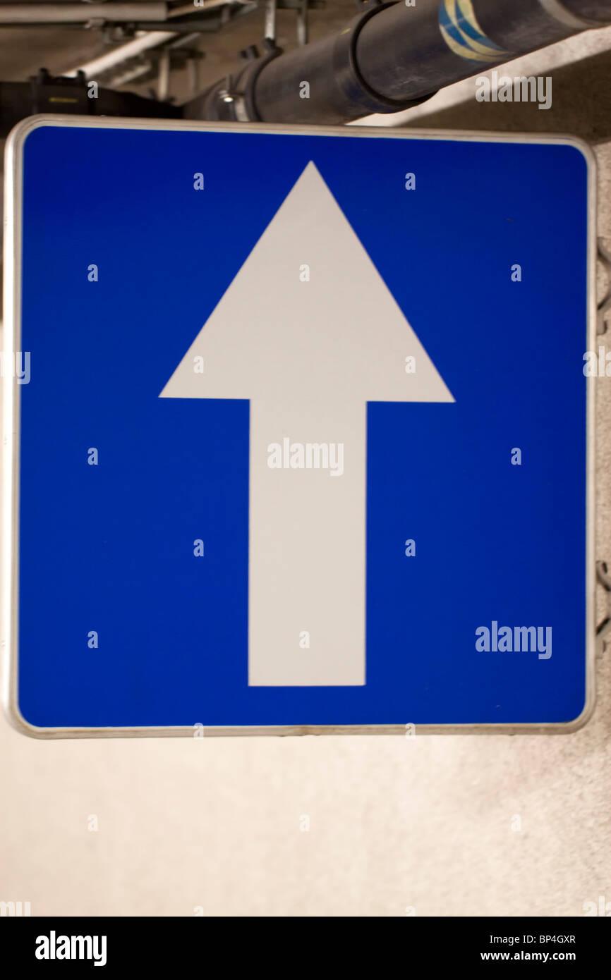Señal de tráfico de color azul con una flecha blanca apuntando hacia arriba Imagen De Stock