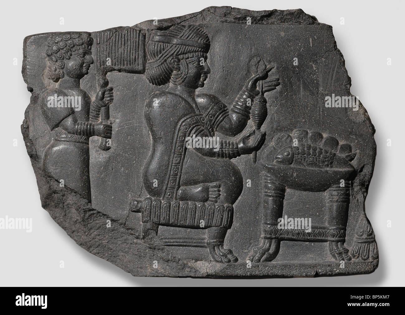Señora Elamite sentado en un taburete de patas de león hilando lana con un husillo. Detrás de ella Imagen De Stock