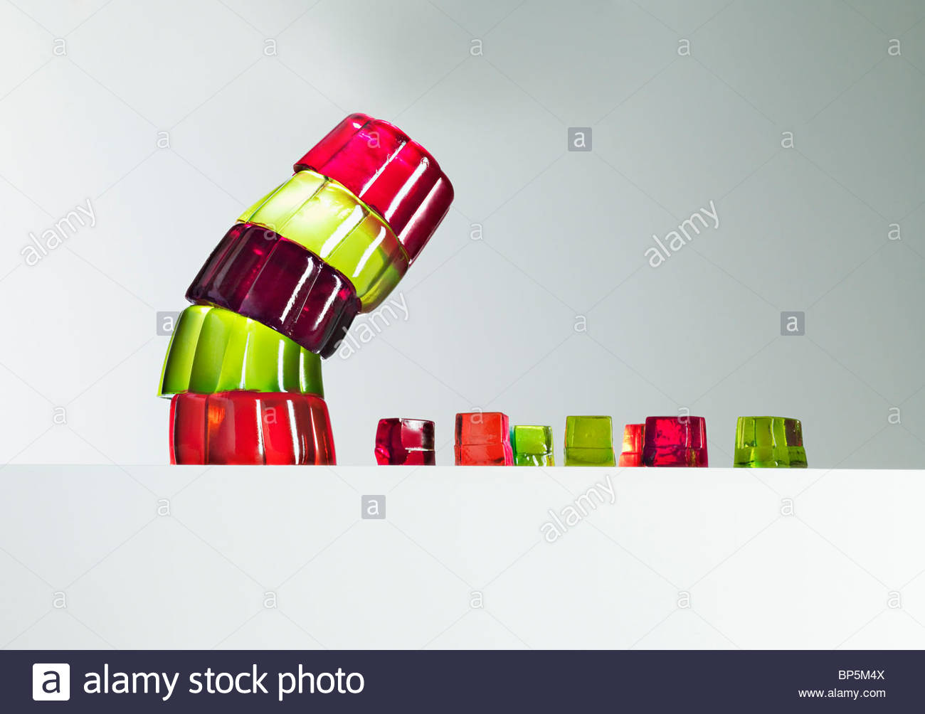 Pila de postres de gelatina vibrante recostada sobre pequeños cubos de postres de gelatina Imagen De Stock