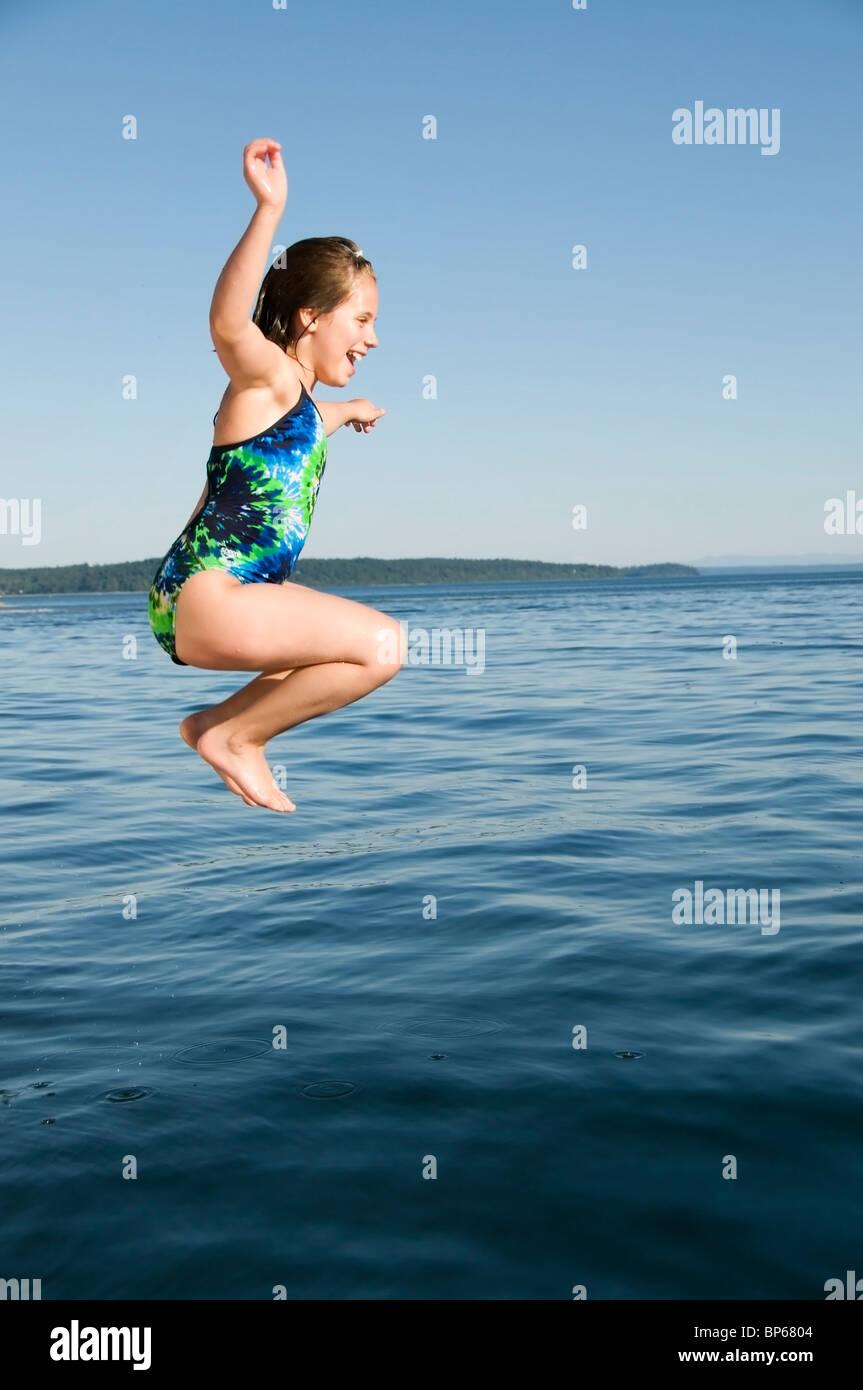 Una niña alegre salta desde un barco en el agua salada McMicken frío cerca de isla en el sur de Puget Imagen De Stock