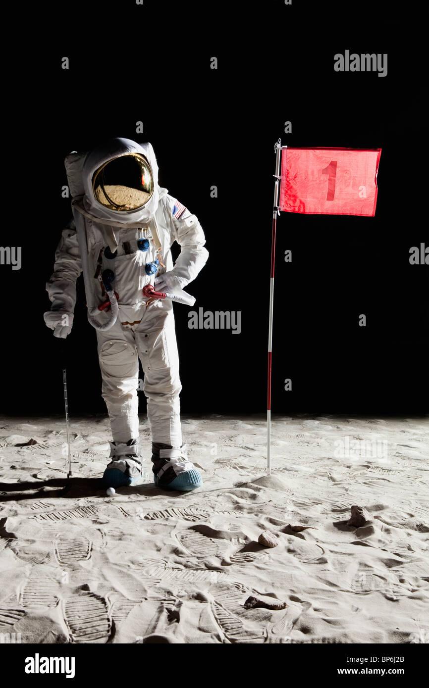 Un astronauta en la luna de pie junto a la bandera del agujero número 1 Foto de stock