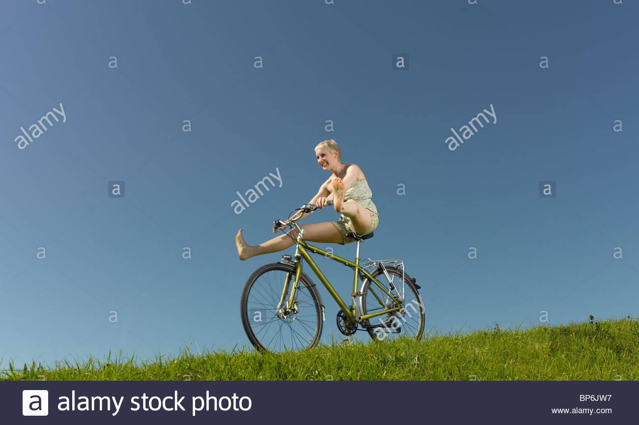 Una mujer irresponsable el descenso sobre una bicicleta en verano Foto de stock
